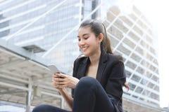 Mulher de negócio asiática nova alegre com o telefone esperto móvel no fundo urbano Internet do conceito das coisas fotos de stock