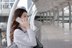 Mulher de negócio asiática nova atrativa que fala no telefone esperto móvel e que guarda o dobrador do original no escritório ext Imagens de Stock Royalty Free