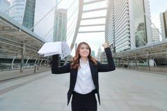 Mulher de negócio asiática nova bem sucedida que levanta o documento ou as cartas em suas mãos no fundo urbano da cidade da const imagens de stock royalty free