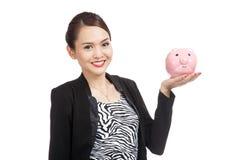 Mulher de negócio asiática nova com um banco de moeda do porco Fotografia de Stock