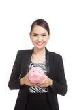 Mulher de negócio asiática nova com um banco de moeda do porco Imagens de Stock