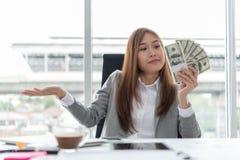 Mulher de negócio asiática nova feliz que guarda o dinheiro fotos de stock