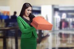 Mulher de negócio asiática nova que abre seu saco de compras Imagem de Stock Royalty Free