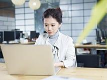 Mulher de negócio asiática nova que trabalha no escritório Fotografia de Stock Royalty Free