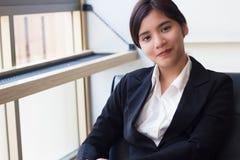 Mulher de negócio asiática nova de sorriso que olha segura e feliz Fotos de Stock Royalty Free