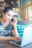 Mulher de negócio asiática que fala no telefone e que trabalha em um lapto fotos de stock