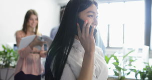 Mulher de negócio asiática que fala no telefonema que guarda originais no funcionamento bonito da mulher de negócios do escritóri vídeos de arquivo