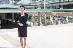 Mulher de negócio asiática que guarda o telefone celular e a conversa sobre o plano de negócios, com espaço da cópia para o texto Fotografia de Stock