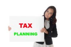 Mulher de negócio asiática que guarda uma bandeira com texto do planeamento fiscal fotos de stock royalty free