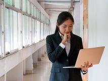 Mulher de negócio asiática que olha o portátil e o pensamento Fotos de Stock