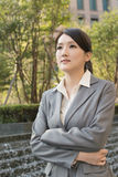 Mulher de negócio asiática que pensa na cidade Foto de Stock Royalty Free