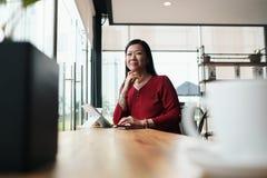 Mulher de negócio asiática que trabalha na barra fora do escritório imagens de stock