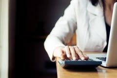 Mulher de negócio asiática que usa a calculadora para explicar Imagem de Stock