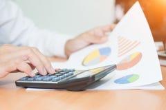 Mulher de negócio asiática que usa uma calculadora para calcular Fotografia de Stock