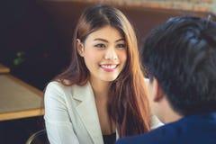 A mulher de negócio asiática sorri em uma maneira amigável de encontrar o negócio t imagem de stock