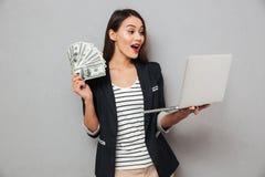 Mulher de negócio asiática surpreendida que guarda o dinheiro e o laptop Fotografia de Stock Royalty Free
