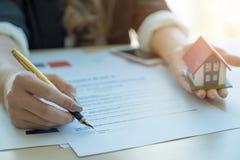 A mulher de negócio assina o contrato e o hoouse m arquitetónico guardar imagem de stock royalty free
