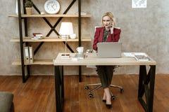 Mulher de negócio atenta séria que tem a chamada relativa a seu trabalho fotografia de stock royalty free