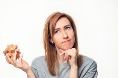 Mulher de negócio atrativa das pessoas de 24 anos que olha confundida com o enigma de madeira Fotografia de Stock Royalty Free