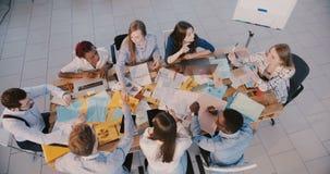 Mulher de negócio atrativa do líder da vista superior que dá a motivação aos executivos felizes na reunião da direção, pr video estoque