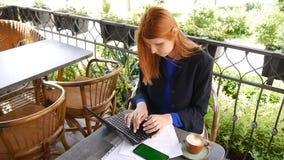 Mulher de negócio atrativa nova que usa o portátil no café Documentos, telefone celular com tela verde e xícara de café no filme
