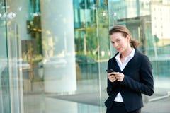 Mulher de negócio atrativa que anda fora com telefone celular Fotografia de Stock