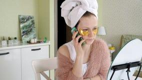 Mulher de negócio atrativa que aplica pontos faciais cosméticos em casa, falando no telefone filme