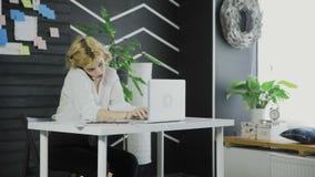 Mulher de negócio atrativa que fala no telefone celular ao datilografar no teclado do portátil no escritório vídeos de arquivo