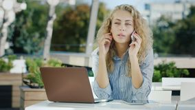 Mulher de negócio atrativa que fala no telefone Sentando-se em um café no terraço, trabalhando com um portátil filme