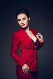 Mulher de negócio atrativa Retrato de uma senhora nova 'sexy' do negócio em um terno vermelho em um fundo escuro Fotografia de Stock Royalty Free