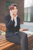 Mulher de negócio autêntica nova que fala ao móbil Fotografia de Stock Royalty Free
