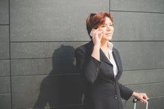 Mulher de negócio autêntica nova que fala ao móbil Foto de Stock Royalty Free