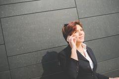 Mulher de negócio autêntica nova que fala ao móbil Fotos de Stock