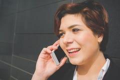 Mulher de negócio autêntica nova que fala ao móbil Imagem de Stock