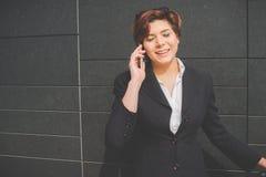 Mulher de negócio autêntica nova que fala ao móbil Imagens de Stock