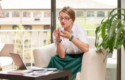 A mulher de negócio bebe o café, apreciando seu café Imagem de Stock