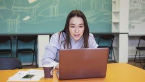 Mulher de negócio bem sucedida que olha a tela e o vencimento do portátil filme