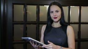 Mulher de negócio bem sucedida que trabalha na tabuleta e video estoque