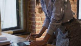 Mulher de negócio bem sucedida que trabalha usando a tabuleta no escritório Senhora nova focalizada do negócio nos vidros com cab filme