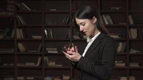 Mulher de negócio bem sucedida que usa o smartphone na biblioteca vídeos de arquivo