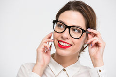 Mulher de negócio bonita alegre nos vidros que fala no telefone celular imagens de stock royalty free