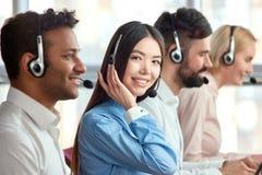 Mulher de negócio bonita alegre nova nos auriculares fotos de stock