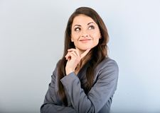 Mulher de negócio bonita do sucesso no terno com o dedo sob a cara que pensa e que olha acima no fundo azul closeup imagem de stock