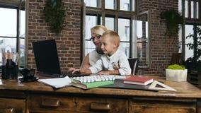 Mulher de negócio bonita de meia idade que senta-se na tabela de madeira e que olha seu neto bonito que jogar o portátil video estoque