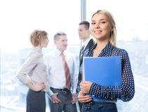 Mulher de negócio bonita na câmera de vista dianteira com a equipe no fundo Imagens de Stock Royalty Free