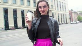 Mulher de negócio bonita nos óculos de sol No café de riso e bebendo da rua de um copo de papel Um forte vento funde com h vídeos de arquivo