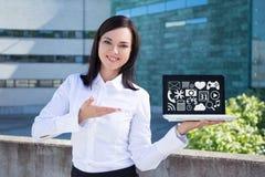Mulher de negócio bonita nova que mostra o portátil com multimédios CI Imagem de Stock