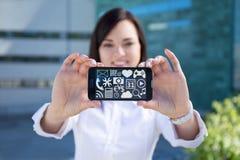 Mulher de negócio bonita nova que mostra o smartphone com multimedi Imagem de Stock