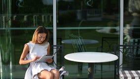 Mulher de negócio bonita nova que senta-se em uma tabela com a tabuleta nas mãos vídeos de arquivo
