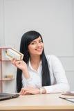 Mulher de negócio bonita nova que senta-se na mesa Imagem de Stock Royalty Free